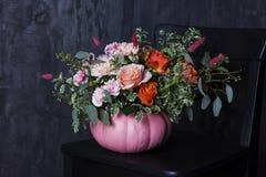在南瓜花瓶的秋天百花香在黑椅子 免版税库存照片