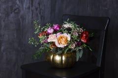 在南瓜花瓶的秋天百花香在黑椅子 图库摄影