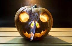 在南瓜头的抽烟的香烟为万圣夜 库存照片