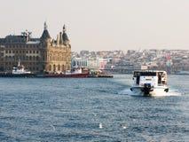 在博斯普鲁斯海峡的一条小船在Haydarpasa火车站背景  库存图片