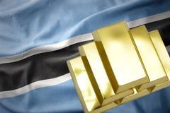 在博茨瓦纳旗子的光亮的金黄金块 库存照片