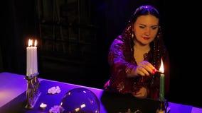 在占卜沙龙的桌上,一件红色礼服的一个吉普赛人点燃在一个被仿造的烛台的蜡烛 股票录像