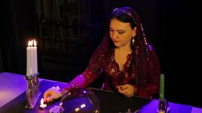 在占卜沙龙的桌上,一件红色礼服的一个吉普赛人点燃在一张黑桌布的蜡烛 股票录像
