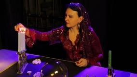 在占卜沙龙的桌上,一件红色礼服的一个吉普赛人点燃在烛台的蜡烛 股票视频