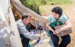 在占卜用的纸牌的算命者-骑士节日的参加者在戈伦公园回答访客问题在以色列 免版税库存图片