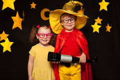 在占星师服装的两个孩子有望远镜的 免版税库存照片