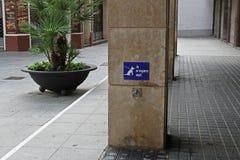 在卡莱利亚尾随与金属圆环的停车处标志在加泰罗尼语的语言 免版税库存照片