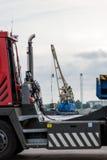 在卡车后现出轮廓有口岸起重机的可看见的浮动平台 免版税库存图片