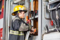 在卡车的女性消防队员定象水水管 免版税库存照片
