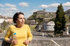 在卢尔德旁边大教堂的美丽的深色的妇女  免版税图库摄影