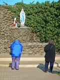 在卢尔德洞穴,宽容寺庙前面的妇女祷告 库存图片