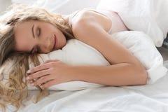 在卧具的平安地微笑的少妇 库存图片