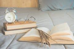 在卧室打开与干花和书架的书在床上 免版税图库摄影