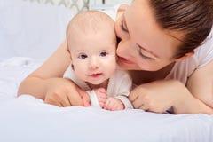 在卧室照顾拥抱与她的婴孩 看在camer 免版税图库摄影