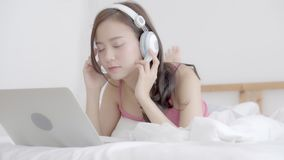在卧室的美丽的年轻亚洲妇女使用手提电脑放松在家听音乐,女孩陈列视频通话闲谈 影视素材