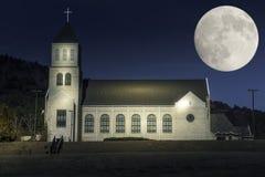 在卫理公会教派的教堂的轻的油漆在supermoon期间 免版税库存图片