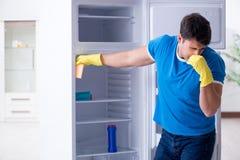 在卫生学概念的人清洁冰箱 免版税库存照片