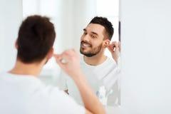 在卫生间供以人员有棉花棒的清洁耳朵 免版税库存图片