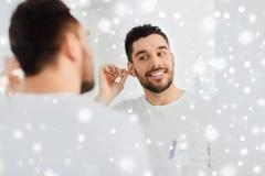在卫生间供以人员有棉花棒的清洁耳朵 库存图片