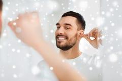 在卫生间供以人员有棉花棒的清洁耳朵 免版税库存照片