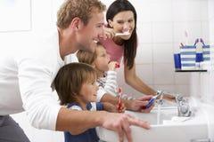 在卫生间掠过的牙的家庭 免版税库存图片