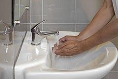 在卫生间水槽的洗涤的手 免版税库存照片