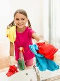 在卫生间的微笑的女孩擦亮的镜子,当清洗房子时 免版税图库摄影