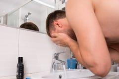 在卫生间里供以人员在他的面孔的喷洒的水 库存图片
