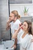 在卫生间里时供以人员刮他的胡子,当应用染睫毛油的妇女 免版税图库摄影