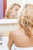 在卫生间里检查她的在镜象反射的白种人妇女画象粉刺有倾向的皮肤 免版税库存图片