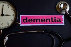 在印刷品纸的老年痴呆与医疗保健概念启发 闹钟,黑听诊器 免版税库存照片