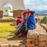 在印加人墙壁,Chinchero,秘鲁上的盖丘亚族人的妇女 免版税库存照片