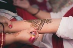 在印度女孩的手上的传统无刺指甲花书刊上的图片 免版税库存照片