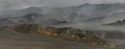 在印度河谷的尘暴:山土坎围拢含沙风,在谷的阴霾,在前景的石土坎, 免版税库存图片
