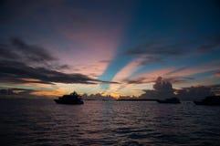 在印度洋的五颜六色的日落:在天空的桃红色黄色和蓝色强光,船的等高在波浪中间的, 免版税库存图片