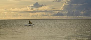 在印度洋的日出 风船在黄色,多云天空下 免版税库存图片