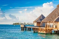 在印度洋的水的木别墅 图库摄影