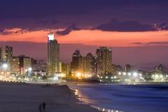 在印度洋浪潮舔在海滩的日落的德班地平线 图库摄影