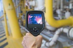 在危险区域的生产操作员调查热点在罚款任何反常条件的近海油和煤气遥远的平台 免版税库存照片