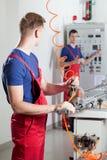 在危险机器修理期间的工厂劳工 免版税库存照片