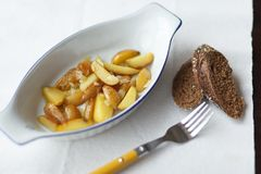 在卵形平底锅的油煎的嫩土豆土豆在桌上 免版税库存照片