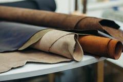 在卷的明亮地色的皮革在白色木背景 皮革工艺 免版税库存照片
