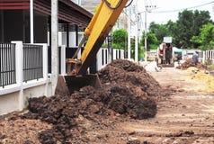在卸载黏土的关闭的机械铁锹在移动在建造场所运转 图库摄影