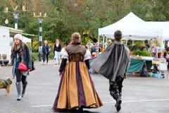 在历史的英国服装的夫妇大踏步走入农夫市场o 免版税库存图片