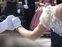 在历史舞蹈期间,关闭在白色手套的夫妇手 舞蹈家美丽和漂亮夫妇  库存照片