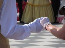 在历史舞蹈期间,关闭在白色手套的夫妇手 舞蹈家美丽和漂亮夫妇  免版税库存图片