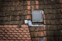 在原始的房子的老红色屋顶的一个小玻璃窗 库存照片