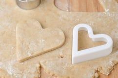 在原始的曲奇饼面团和重点形状的心形的曲奇饼切割工 库存照片