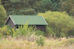 在原野中间的小木小屋 库存图片