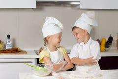 在厨师服装的逗人喜爱的微笑的孩子 库存照片